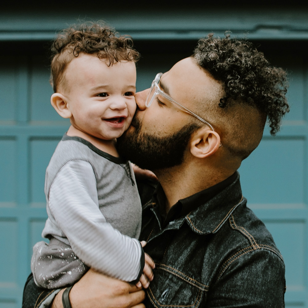 African American father kissing toddler son